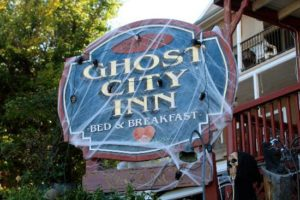 The Ghost City Inn Sign with cobwebs all around it.