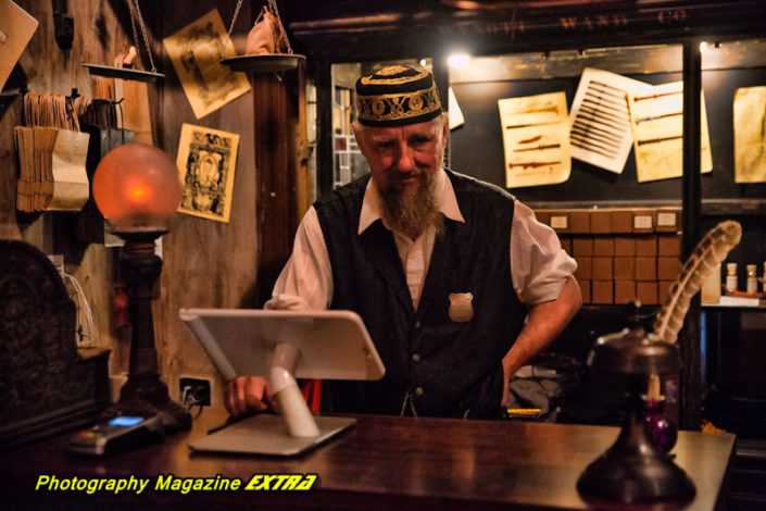OL Harry Potter looking man behind a desk in 1800's attire with beard and hat at ghost tour