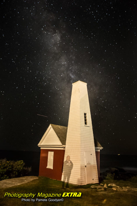 Pemaquid Point lighthouse, Maine, with famous photographer Pamela Goodyer next to the lighthouse with the milky way above her head in the sky